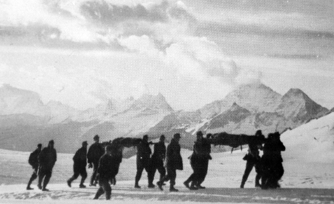 Seriously wounded German mountain troops are carried back down to a dressing-station on stretchers over the Chotiu-Tau Pass in the Caucasus in 1942